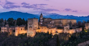 Illuminated Arabic Alhambra palace in Granada,Spain with Sierra Nevada snowy mountains in background