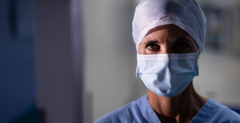 Portrait of a Caucasian female surgeon looking at the camera with an operation mask in the operation room