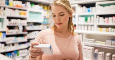 pregnancy, medicine, people, healthcare and expectation concept - happy pregnant woman with medication at pharmacy