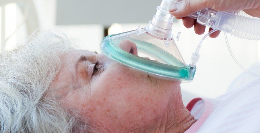 Senior patient receiving oxygen mask in a hospital