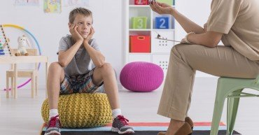 Small boy sitting on a pouf, talking with a psychotherapist