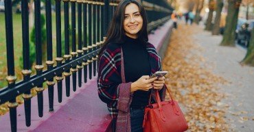 girl using her cell phone while walking through the park during autumn