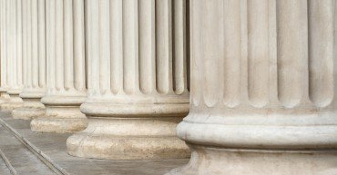 Horizontal perspective view close up of classical building marble white columns with stairs