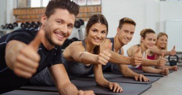 gruppe im fitness-studio zeigt daumen hoch