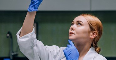 Female medical or scientific researcher or woman doctor looking at a test tube of clear solution in a laboratory.