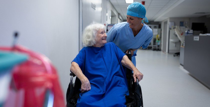 Front view of a Caucasian female surgeon talking with a Caucasian senior female patient sitting in a wheelchair in hospital corridor