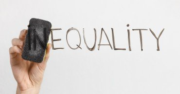 Equality concept. Man cleaning part In in word Inequality with sponge, written on glass board, copy space