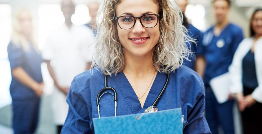 Portrait of young woman wearing doctor uniform standing in a hospital.