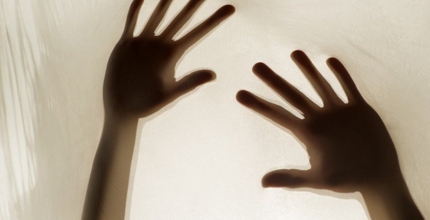 Photographic representation of violence on women, hands against sheet