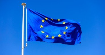 EU flag. European Union flag on a flagpole waving on a bright blue sky background