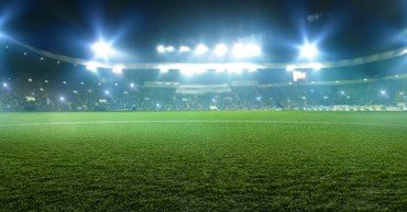 Football stadium, shiny lights, view from field grass. Turf, nobody on playground, tribunes with game fans on background