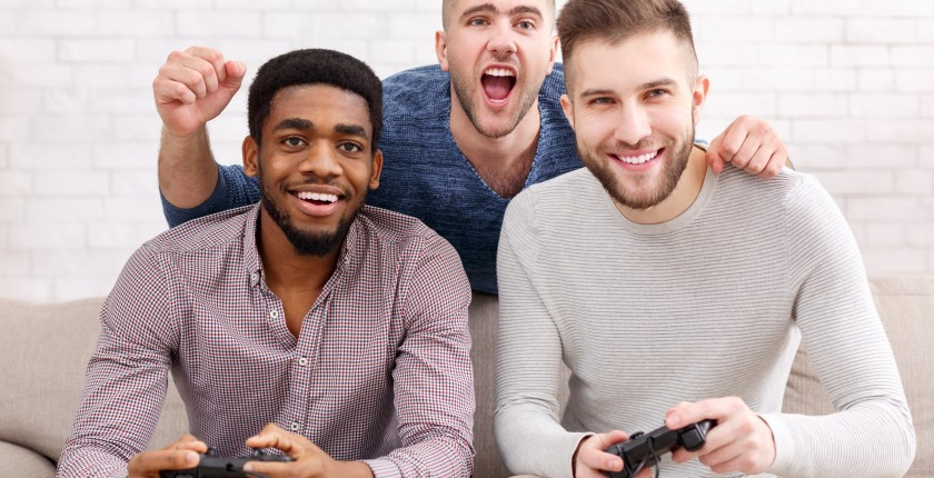 Gamers. Excited men playing video game, meeting and having fun at home