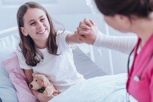 High angle of girl with plush toy smiling and giving a high five to a nurse in the hospital